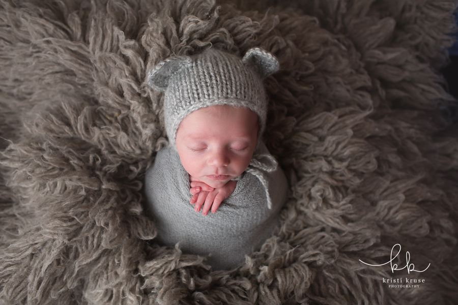 Newborn baby boy wrapped in gray wrap with gray knit bear hat