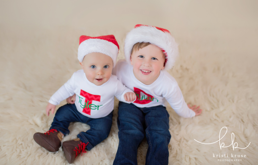 3 year old and 6 month old brothers in white shirts with initials and blue jeans wearing santa hats