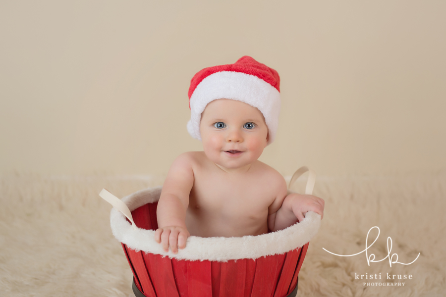 6 month old baby boy sitting in santa bucket with Santa hat on