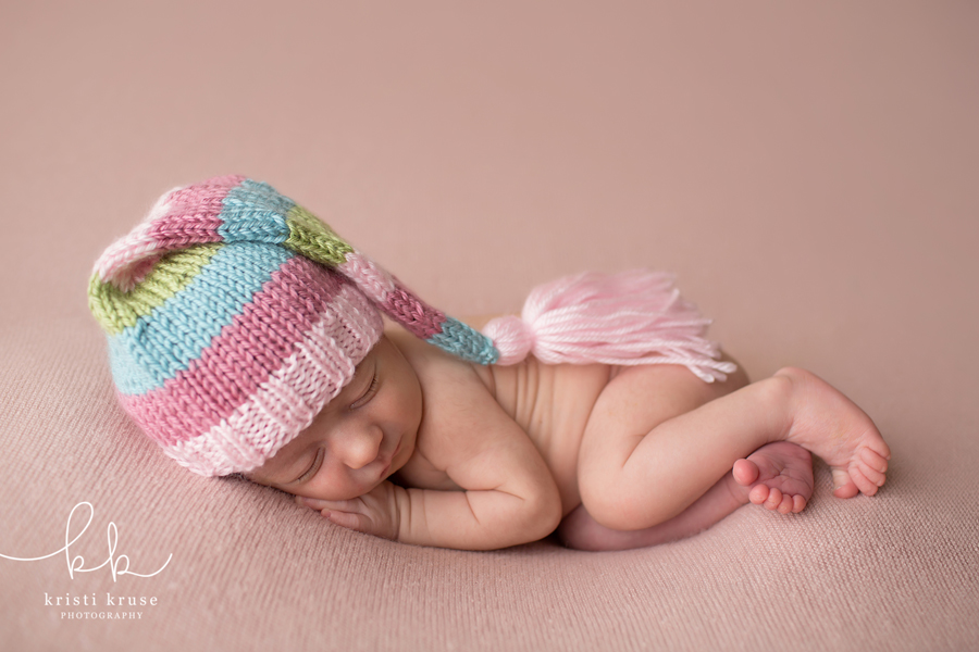 Newborn baby posed on pink blanket with striped sleepy cap