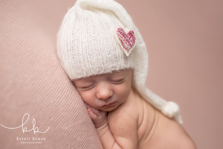 3 week newborn on pink blanket with heart