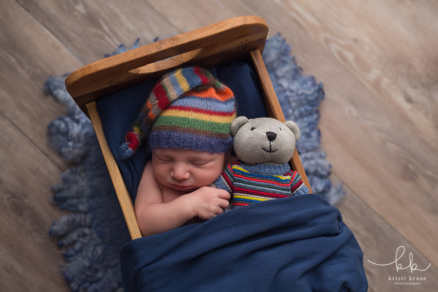 Baby boy with striped hat laying in smal wooden bed with teddy bear in matching sweater