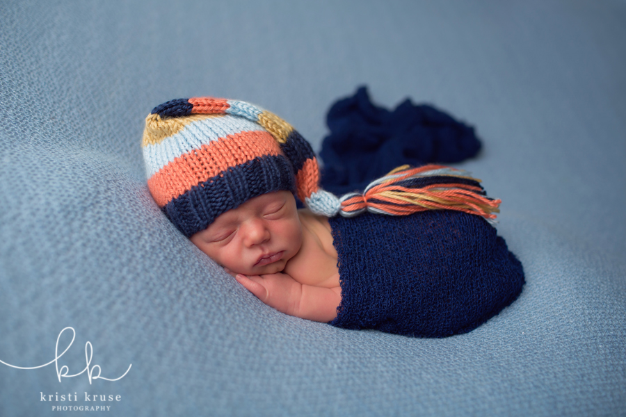 Baby boy on light blue blanket with striped knit hat and dark blue wrap