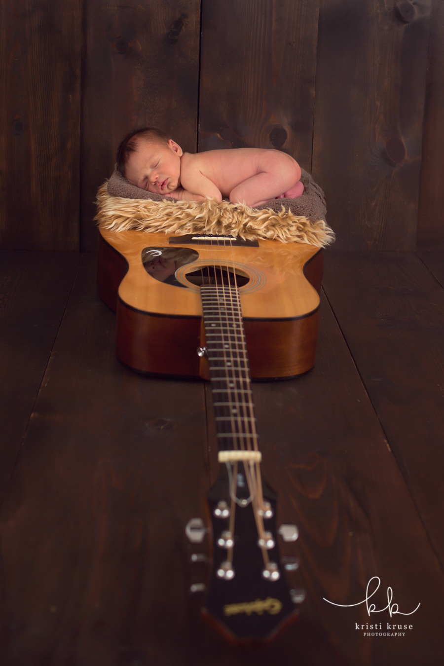 Baby boy laying on his father's guitar