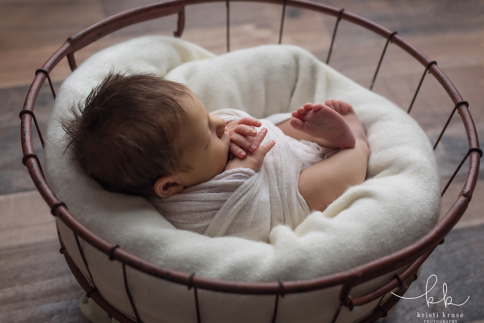 6 month baby boy wrapped in white in basket