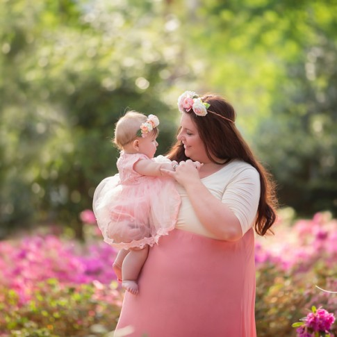 Mother holding 6 month old daughter wearing flower crown. Both are standing in a flower garden